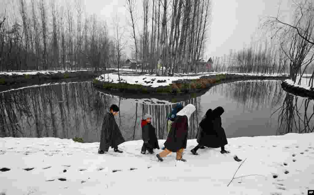 Anak-anak Kashmir berjalan di atas jalanan bersalju di kota Srinagar, India.