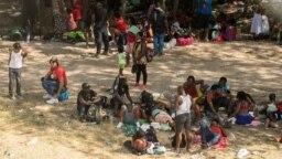 Migrantes solicitantes de asilo descansan a la sombra cerca del Puente Internacional entre México y Estados Unidos, donde los migrantes solicitantes de asilo esperan ser procesados en Del Rio, Texas, EE. UU., el 15 de septiembre de 2021.