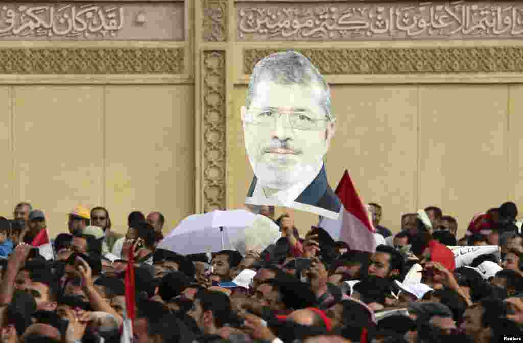 Supporters of Egyptian President Mohamed Morsi chant slogans and carry an image of Morsi, during a protest praising a new decree he issued on Thursday, in front of the presidential palace in Cairo, Egypt, November 23 , 2012.