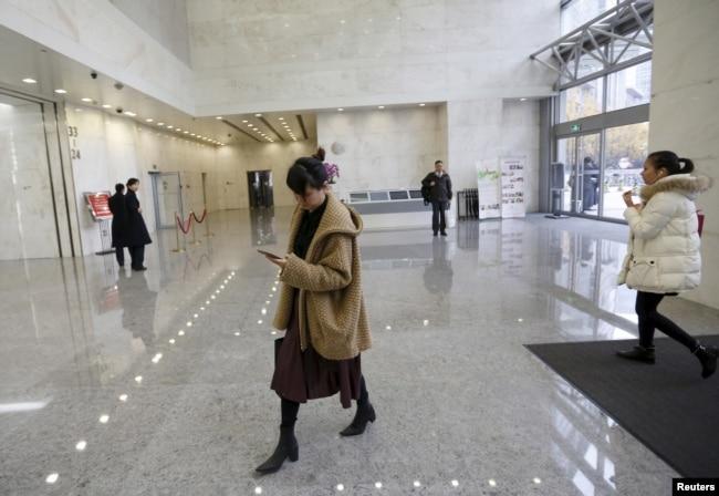 在北京某寫字樓裡走路低頭看手機的中國女性