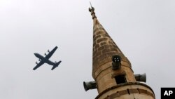 With a mosque's minaret in the foreground, a United States Air Force cargo plane takes off from Incirlik Air Base, on the outskirts of the city of Adana, southern Turkey, July 30, 2015.