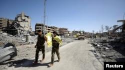 Combatientes de las furzas democráticas de Siria caminan por una calle de Raqqa, Siria, el martes, 17 de octubre de 2107.
