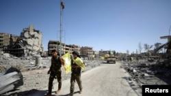 Pejuang Pasukan Demokratik Suriah berjalan di sepanjang jalan di Raqqa, Suriah, 17 Oktober 2017.