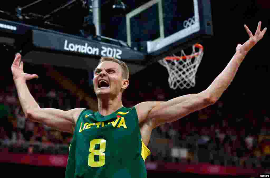 Lithuania's Renaldas Seibutis celebrates a basket against Tunisia during their men's preliminary round Group A basketball match.
