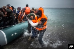 FILE - Refugees and migrants disembark on a beach after crossing a part of the Aegean sea from Turkey to the Greek island of Lesbos.
