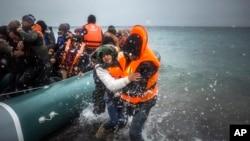 Des réfugiés venus de Turquie débarquant sur une plage de l'ile grecque de Lesbos, après une traversée de la mer Egée, le 12 février 2016. (AP Photo/Santi Palacios, File)