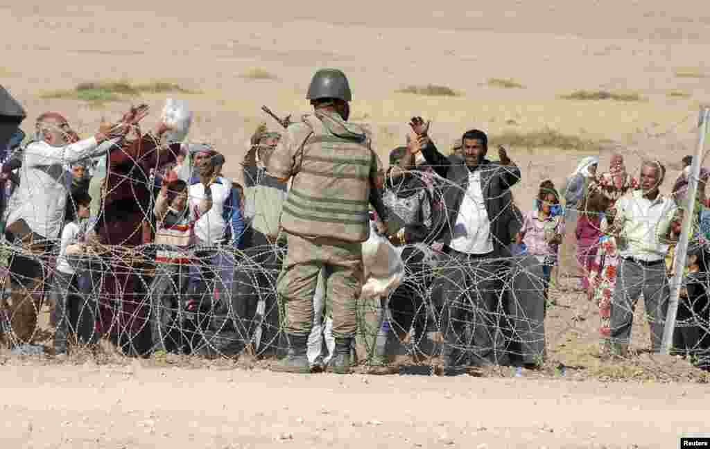 A Turkish soldier stands guard as Syrian Kurds wait behind the border fence to cross into Turkey near the southeastern town of Suruc in Sanliurfa province, September 19, 2014. Several thousand Syrian Kurds began crossing into Turkey on Friday fleeing Isla