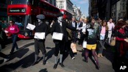 FILE - Men dressed as 1920s newspaper boys with 'greyscale' make up pose for photographs as they hand out specially made newspapers that feature two chapters of the latest novel featuring fictional Belgian detective Hercule Poirot outside Oxford Circus underground train station in London, May 21, 2015.
