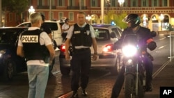 Police officers seal off the area of an attack after a vehicle drove onto the sidewalk and plowed through a crowd of revelers who'd gathered to watch Bastille Day fireworks in the French resort city of Nice, July 15, 2016.
