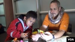 Ken Fowler teaches origami to an interested student in Boulder, Colorado