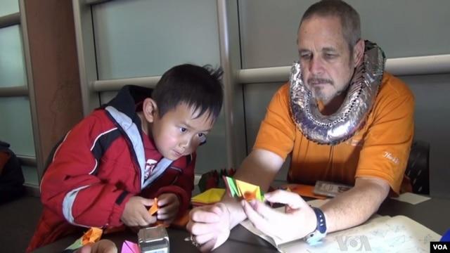 Ken Fowler memberikan tips-tips origami kepada seorang murid. Origami, telah membawa Ken sembuh dari depresi yang pernah dideritanya.