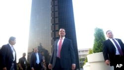 The eldesr son of U.S. President Donald Trump, Donald Trump Jr., center, stands in front of Trump Towers after its inauguration in Pune, India, Feb. 21, 2018.