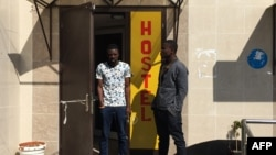 Sodiq Olamilekan, left, a 25-year-old Nigerian, stands next to his 21-year-old brother, Ismail, at a door of a hostel in Moscow, July 12, 2018.