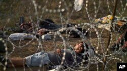 FILE - Afghan refugees sleep next to razor-wire barrier at the Serbian side of Hungary's border fence with Serbia, Sept. 17, 2015.
