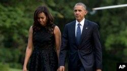 바락 오바마(오른쪽) 미국 대통령과 부인 미셸 여사가 12일 텍사스주 댈러스 총기피격 경찰관 영결식에 참석한 뒤 백악관으로 돌아와 전용헬기에서 내려 걷고 있다.