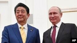 Presiden Rusia Vladimir Putin (kanan) dan PM Jepang Shinzo Abe berjabat tangan sebelum berlangsunya pembicaraan terkait sengketa wilayah di Kremlin, Moskow, Rusia, 22 Januari 2019.