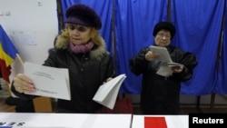 Dua warga Rumania tengah bersiap memberikan suaranya dalam Pemilu Parlemen di salah satu TPS di Bucharest (9/12).