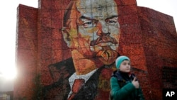 FILE - A boy pauses for photos in front of a mosaic portrait of Vladimir Lenin on Feb. 20, 2014, in Sochi, Russia. (AP Photo/Jae C. Hong)