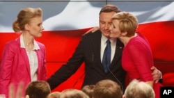 Andrzej Duda, candidate of the conservative opposition Law and Justice party, receives a kiss from his wife Agata, right, as his daughter Kinga, left, watches, after the announcement of the first exit polls in the first round of the Polish presidential elections in Warsaw, Poland, Sunday, May 10, 2015.