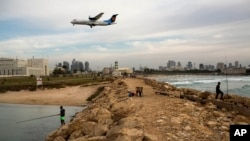 Israelis fish in the Mediterranean sea as aircraft prepares to land in Sde Dov airport in Tel Aviv, Nov. 24, 2013.
