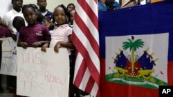 Timoun ki kanpe akote yon drapo ameriken ak drapo ayisyen; yo kenbe pankat nan men yo pou mande renouvle Estati Pwoteksyon Tanporè pou ayisyen yo. (TPS), Miami, 6 novanm 2017.