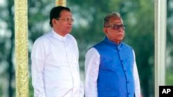 Sri Lankan President Maithripala Sirisena reviews a Guard of Honor, with Bangladesh President Abdul Hamid, in blue jacket, at the Hazrat Shahjalal International Airport in Dhaka, Bangladesh.