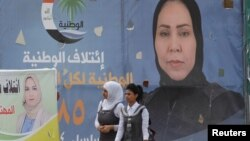 Girls walk past campaign posters of candidates ahead of parliamentary elections, in Tikrit, Iraq, April 29, 2018.