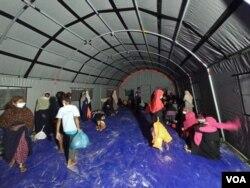 Pengungsi Rohingya memasuki tenda darurat yang dipasang oleh pihak berwenang di Kabupaten Aceh Timur, Jumat, 4 Juni 2021. (Foto: VOA/Anugrah)