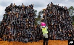 A man pours fuel on a pile of 5,250 illegal weapons before they were burned by Kenyan police in Ngong, near Nairobi, in Kenya, Nov. 15, 2016.