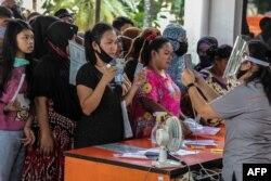 Sejumlah warga menerima bantuan langsung tunai di tengah pandemi virus corona di Medan, Sumatra Utara, 18 Mei 2020. (Foto: AFP)