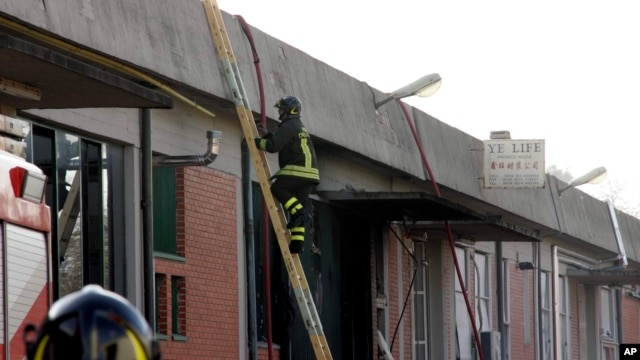A firefighter climbs a ladder to get to the roof of a Chinese-run garment factory where fire swept through on Sunday, in Prato, near Florence, Italy, Dec. 1, 2013.