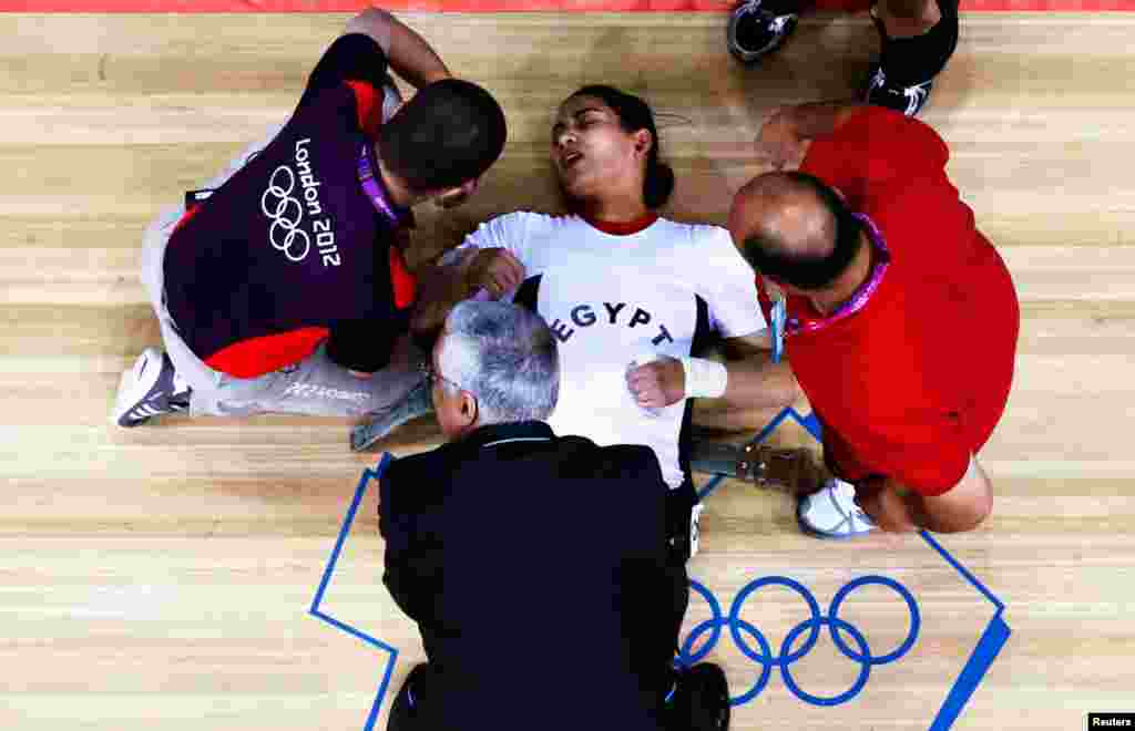 Egypt's Khalil K Abir Abdelrahman is assisted after failed attempt on the women's group A weightlifting competition.