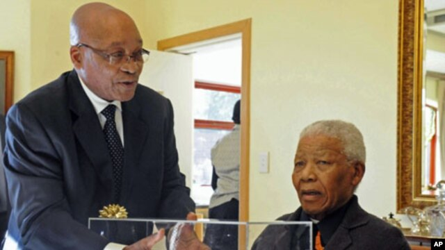 South African President Jacob Zuma presents former President Nelson Mandela with a gift - an architect's rendering of the Nelson Mandela Legacy Bridge - (file photo)