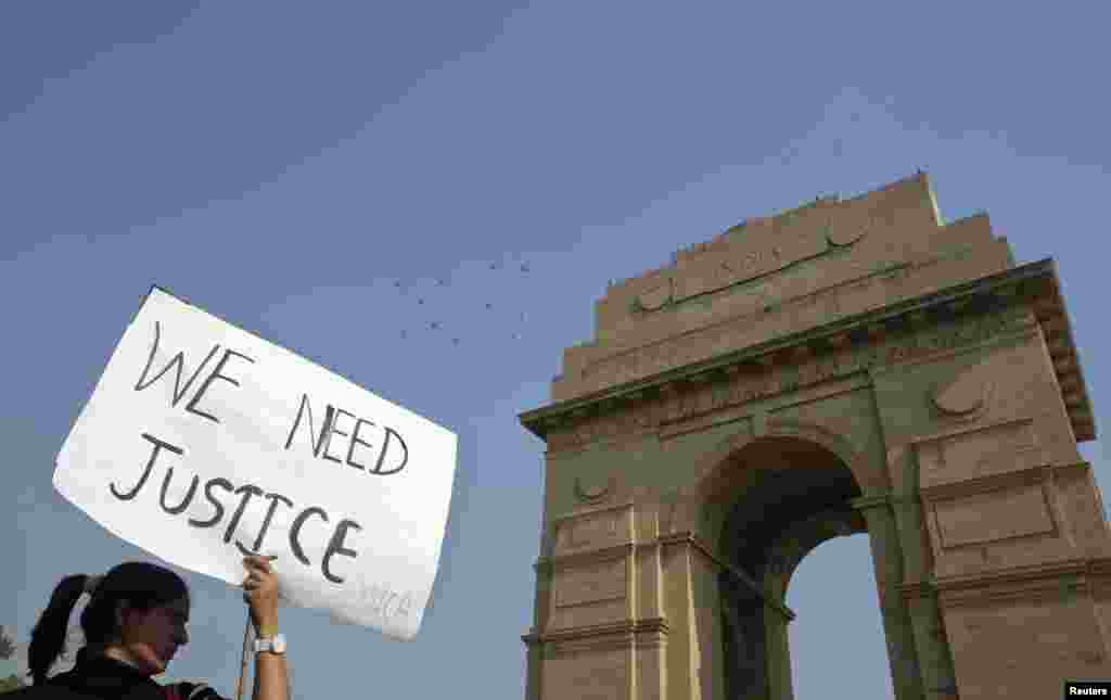 A demonstrator holds a placard in front of India Gate as she takes part in a protest rally organized by various women's organisations in New Delhi, India, December 21, 2012.