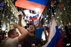 Russian soccer fans celebrate the national team victory after the group A match between Russia and Egypt during the 2018 soccer World Cup in Moscow, Russia, early on June 20, 2018..