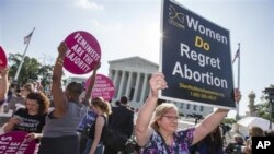 People on both sides on the abortion issue gather outside the U.S. Supreme Court on Monday