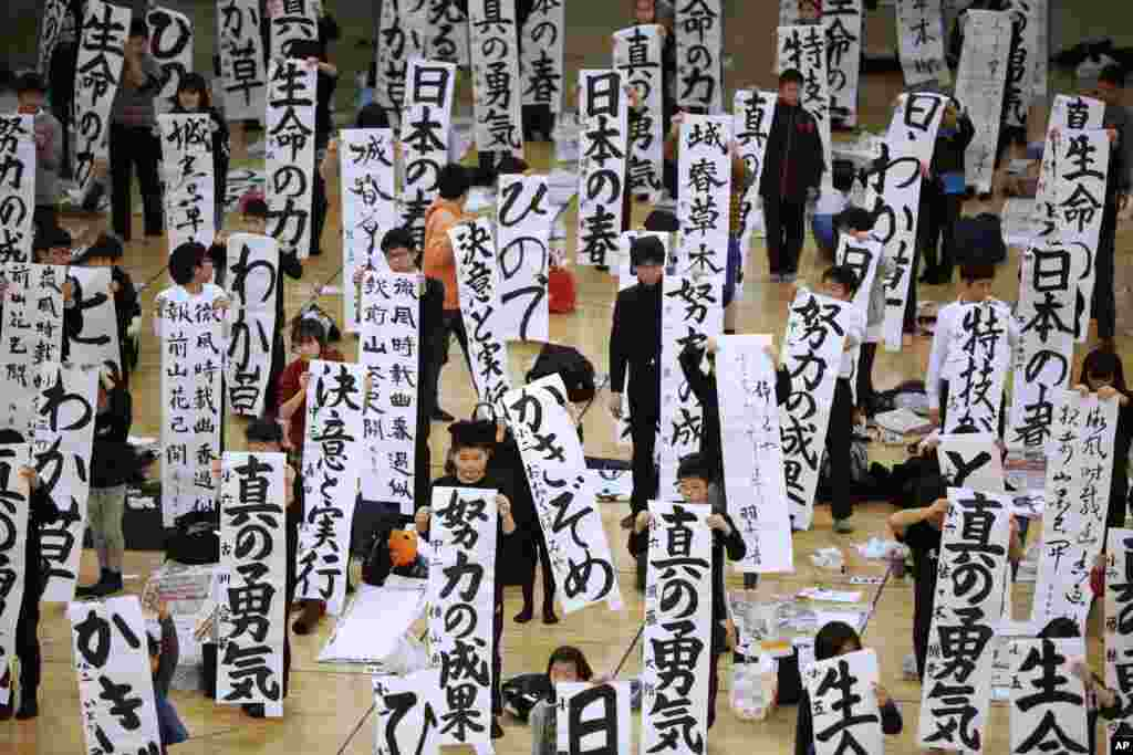 Participants show off their traditional Japanese calligraphy works during the annual New Year's calligraphy contest at the Budokan martial arts hall in Tokyo.