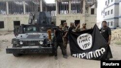 지난해 7월 이라크 정부군이 안바르 주에서 수니파 무장단체 ISIL이 점령한 지역을 탈환한 후 ISIL 깃발을 거꾸로 들고 있다. (자료사진)