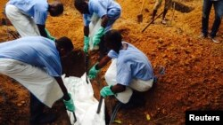 Volunteers lower a corpse, which is prepared with safe burial practices to ensure it does not pose a health risk to others and stop the chain of person-to-person transmission of Ebola, into a grave in Kailahun, Sierra Leone, July 18, 2014.