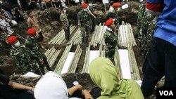 Tentara Indonesia berdiri di antara jenazah korban letusan gunung Merapi di Umbulharjo, Yogyakarta, Indonesia.