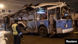 A policeman watches as a bus, destroyed in an earlier explosion, is towed away in Volgograd on December 30, 2013.