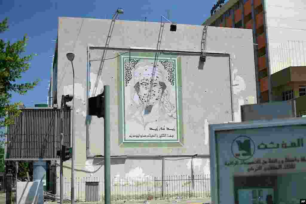 An image of Gadhafi with bullet holes in downtown Tripoli (VOA Photo - J. Weeks)