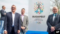 President of the Hungarian Olympic Committee Zsolt Borkai, left, Chairman of the Budapest 2024 bid Balazs Furjes, second left, and Budapest Mayor Istvan Tarlos, right, pose in front of the logo of host city candidate Budapest for the 2024 Olympic and Par