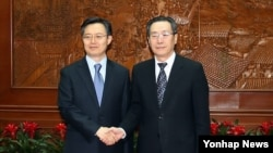 한국 측 6자회담 수석대표인 황준국 외교부 한반도평화교섭본부장이 지난해 4월 베이징에서 중국 측 6자회담 수석대표인 우다웨이 한반도사무특별대표과 만나 악수하고 있다. (자료사진)