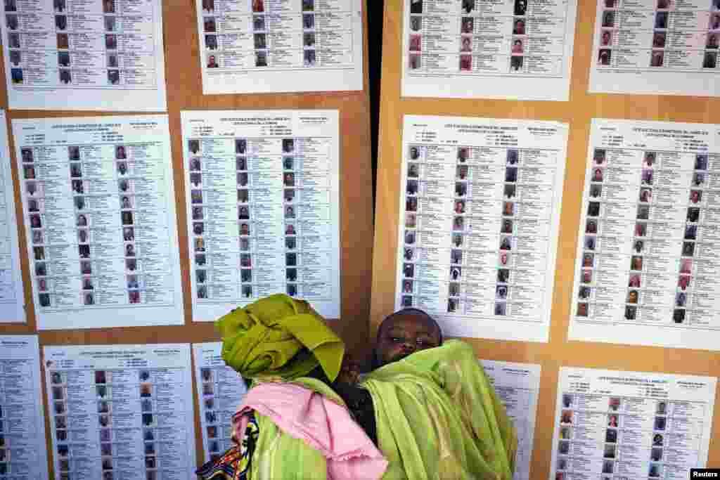 A woman holding a baby searches for her name on a list of eligible voters at an election center in Bamako, Mali.