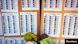 A woman holding a baby searches for her name on a list of eligible voters at an election center in Bamako, July 23, 2013.