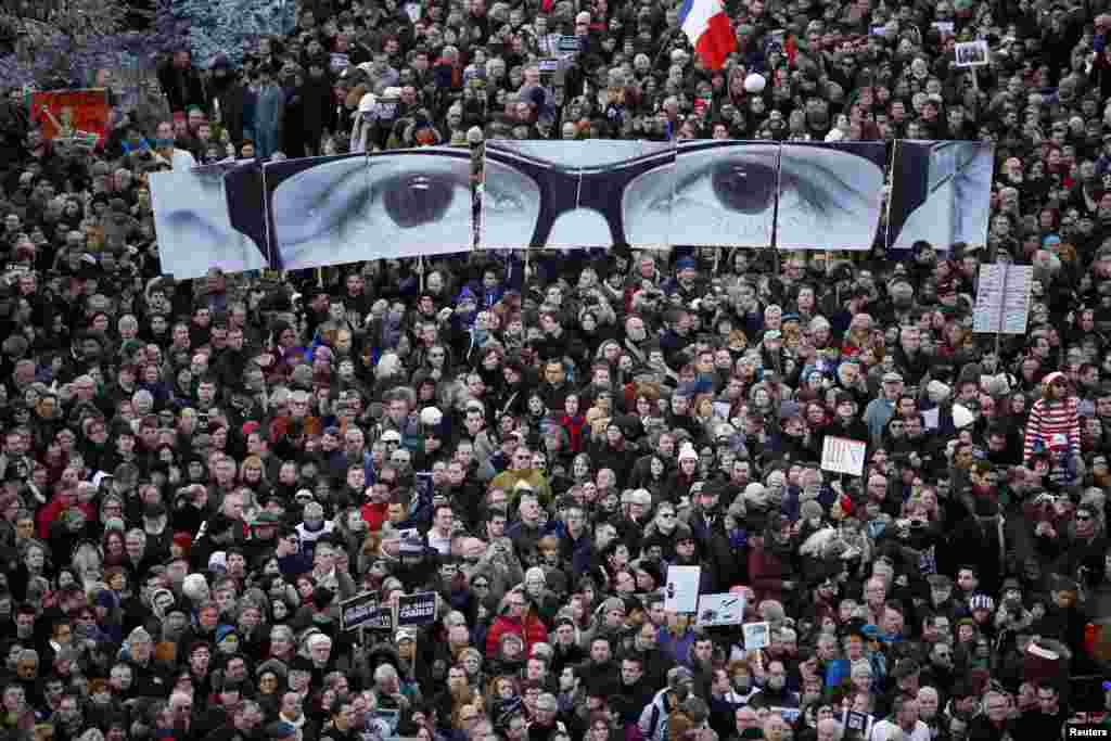 "People hold panels to create the eyes of late Charlie Hebdo editor Stephane Charbonnier, known as ""Charb"", as hundreds of thousands of French citizens take part in a solidarity march (Marche Republicaine) in the streets of Paris."