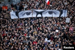 "FILE - People hold panels to create the eyes of late Charlie Hebdo editor Stephane Charbonnier, known as ""Charb"", as hundreds of thousands of French citizens take part in a solidarity march in the streets of Paris, Jan. 11, 2015."