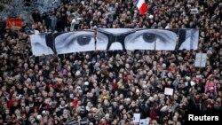 Warga memegang panel untuk menciptakan gambar mata editor Charlie Hebdo, Stephane Charbonnier, saat ratusan ribu warga ambil bagian dalam pawai solidaritas di Paris (11/1). (Reuters/Charles Platiau)
