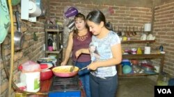 Under the supervision of her mother-in-law, left, Estrella, married at 13, learns to cook. She wakes up early to have her husband's coffee ready by 5:40 a.m. or 6 a.m. (Photo by Ery Acuna Meneses for VOA News)